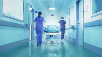 hospital staff wheel away empty gurney