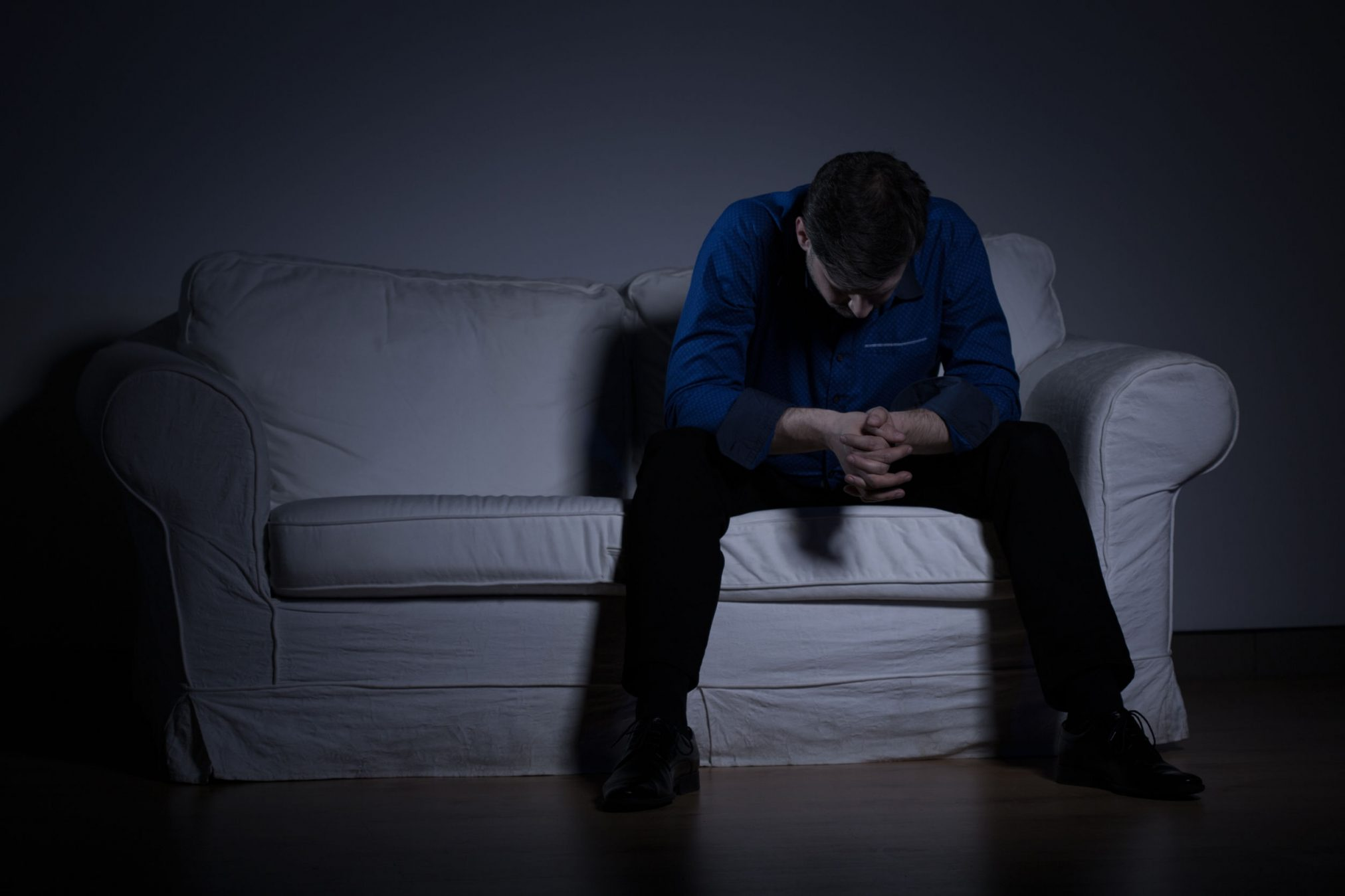 sad man on couch in dark