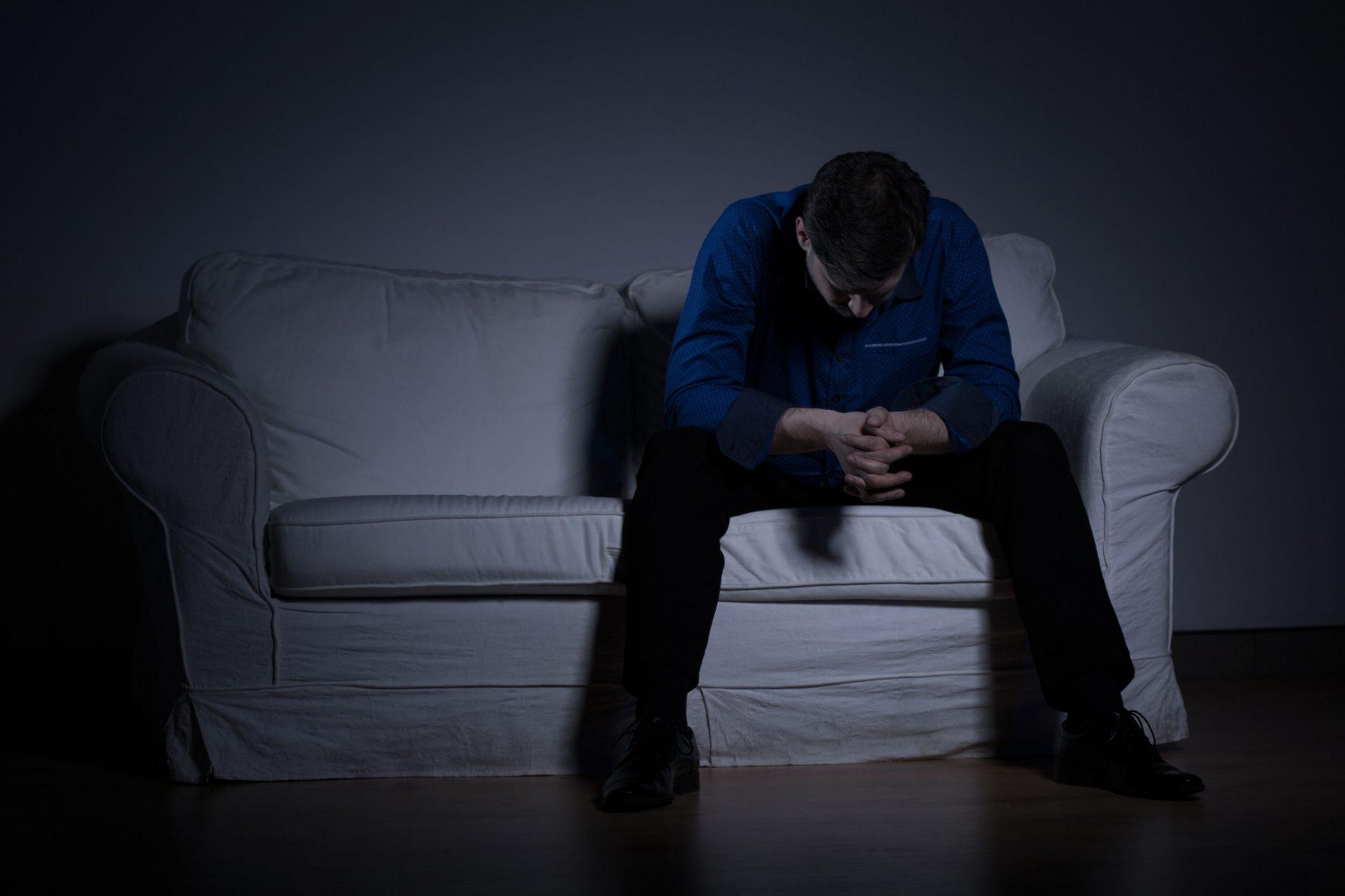 sad man on couch in dark