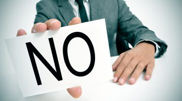 man holding 'no' sign