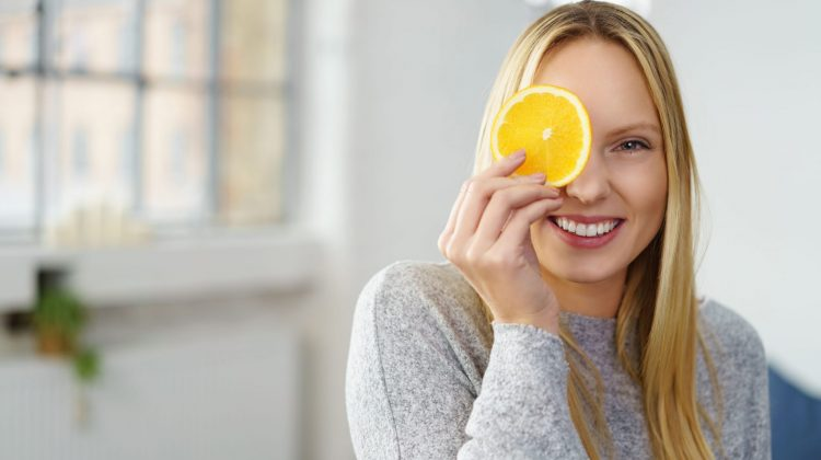 young woman holding slice of lemon to eye