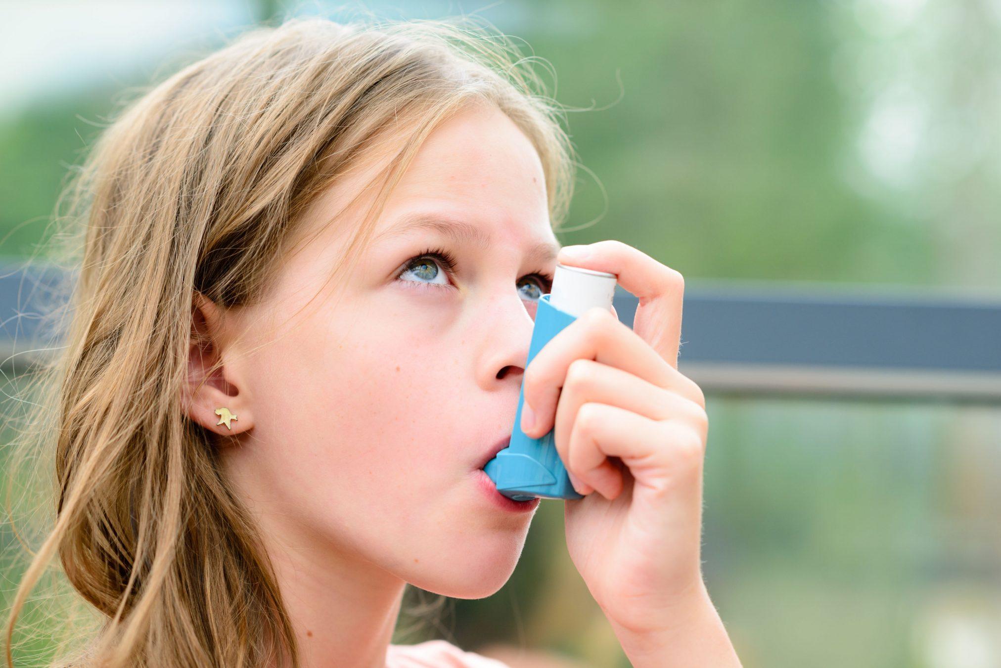 girl using asthma puffer