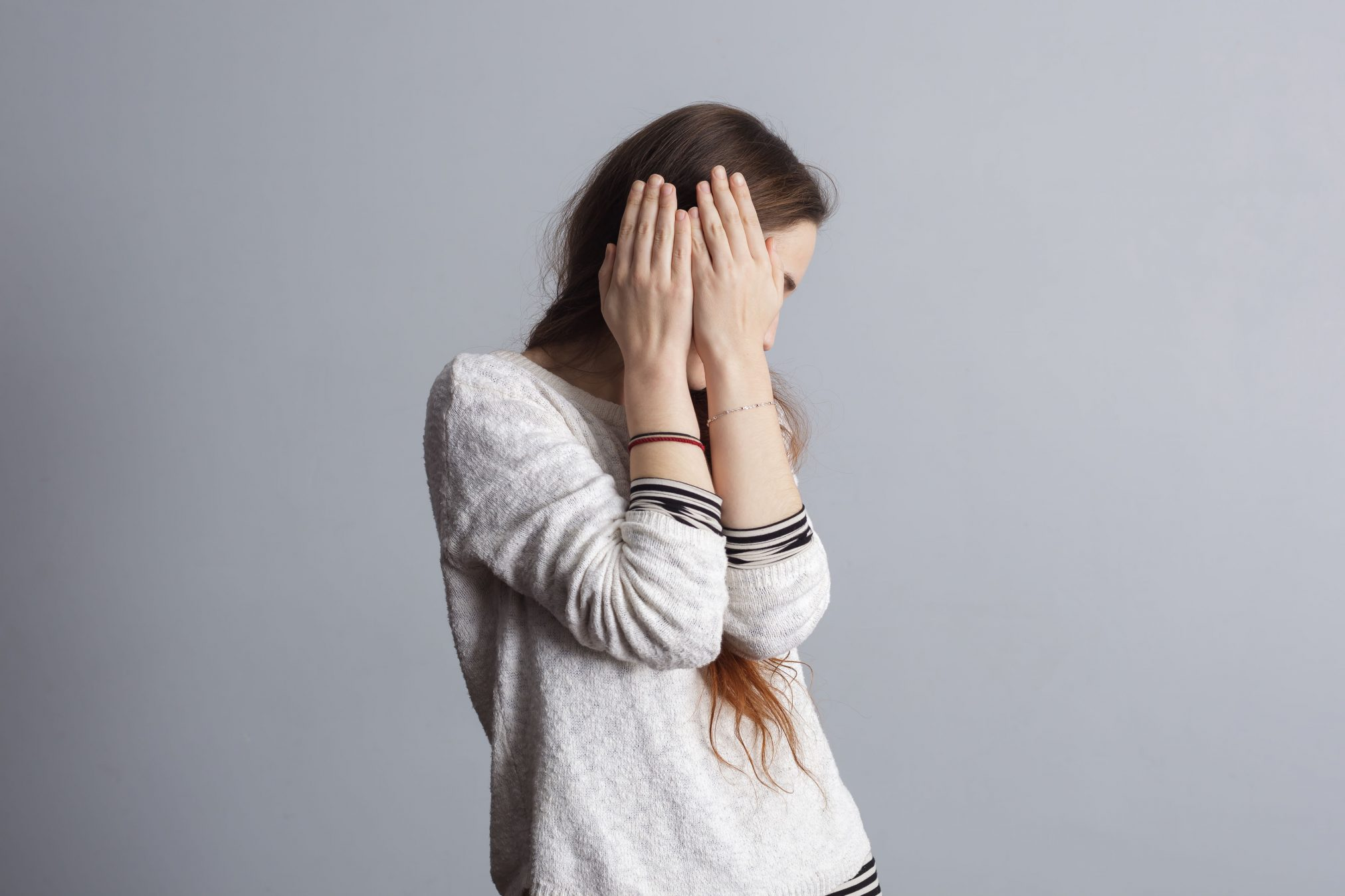 shy embarrassed young woman hiding face covering face