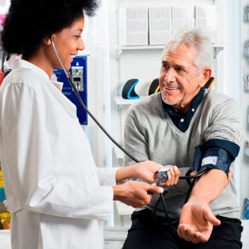 pharmacist checking blood pressure of senior man