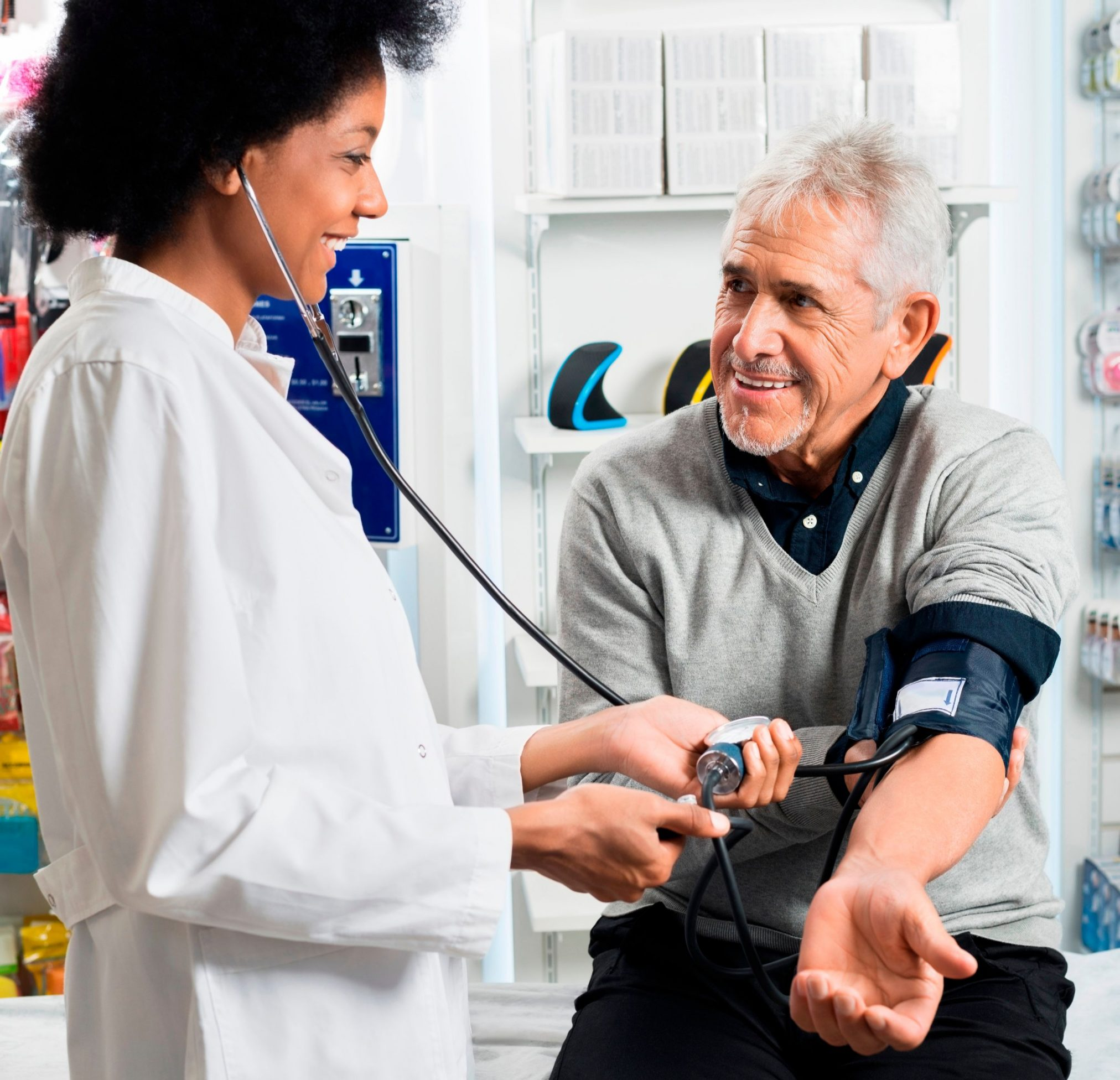 pharmacist checking blood pressure of senior man