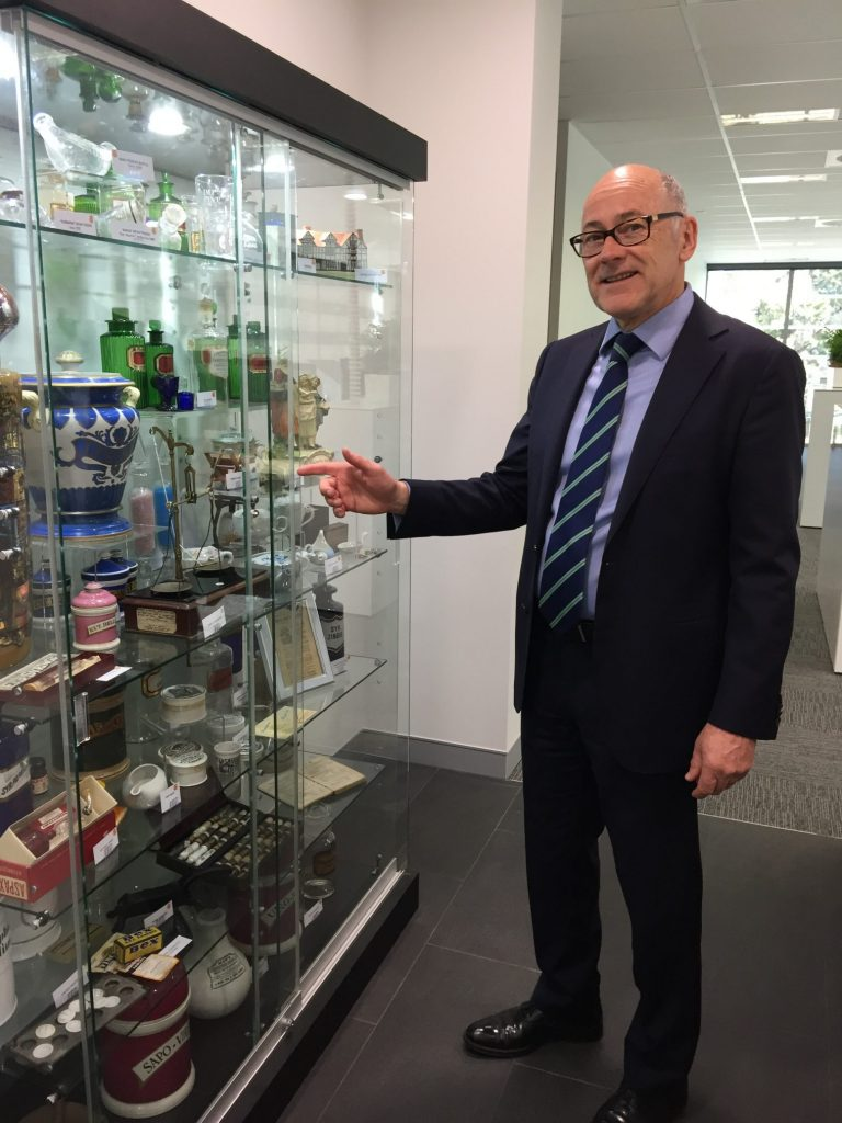 PDL CEO David Brown shows off the display of historic artefacts sponsored by PDL at PSA Pharmacy House in Canberra.