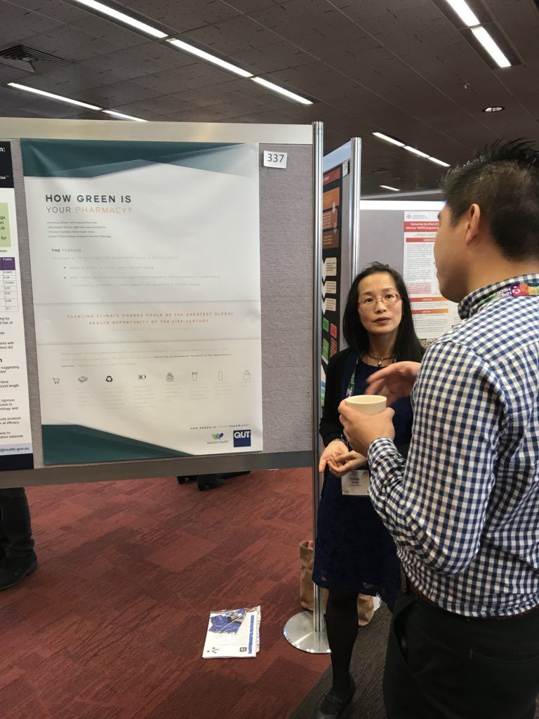 Grace Wong discusses her poster with colleagues.
