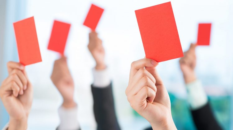 business owners holding up red cards for reprimand