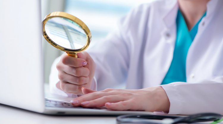 health professional at computer with magnifying glass
