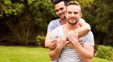 happy gay couple in park