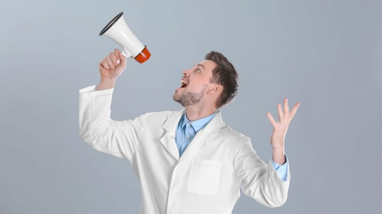 white coat professional shouting into megaphone