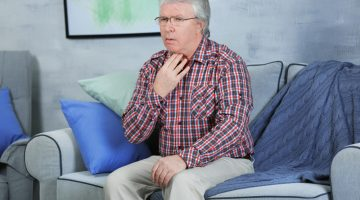 older man holding sore throat