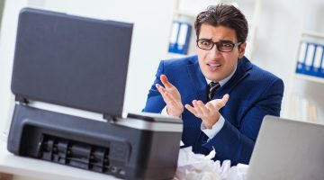 confused businessman with fax machine