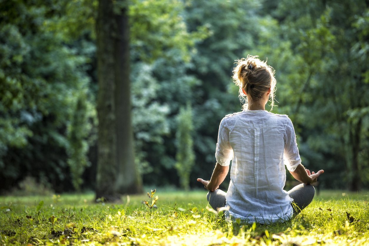 Young blonde woman meditating in the park