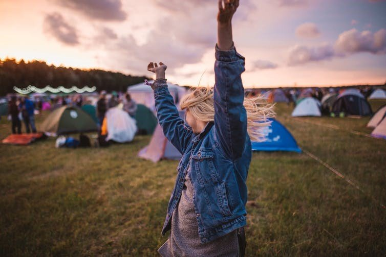 woman dances at music festival at dusk