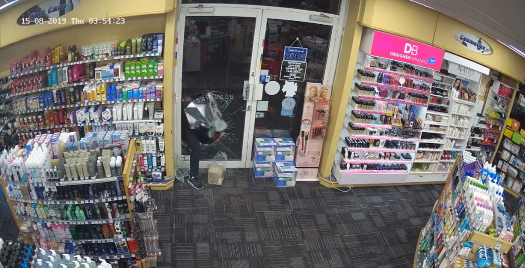 man kicking his way into pharmacy through hole in glass front door