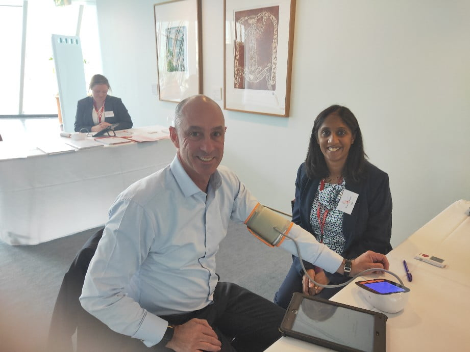 Pharmacist Bev Mistry-Cable tests Senator David Van from Victoria for an irregular heartbeat