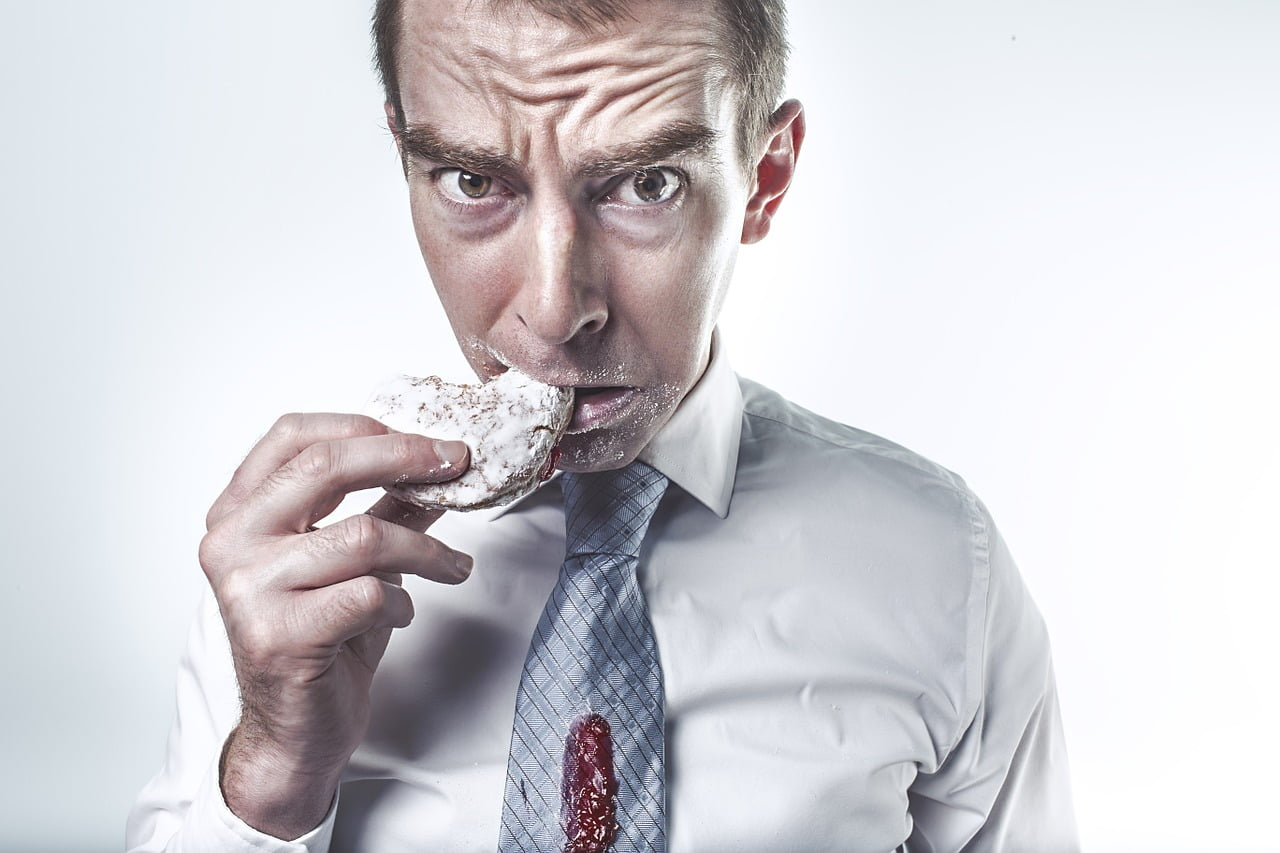 a man eating a biscuit looking worried