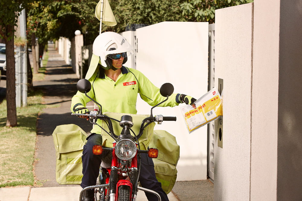 Postie on motorbike holding Express Post package