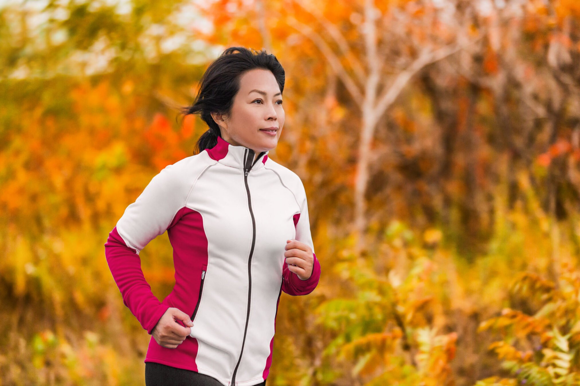 Fiftysomething woman going for jog against autumn background