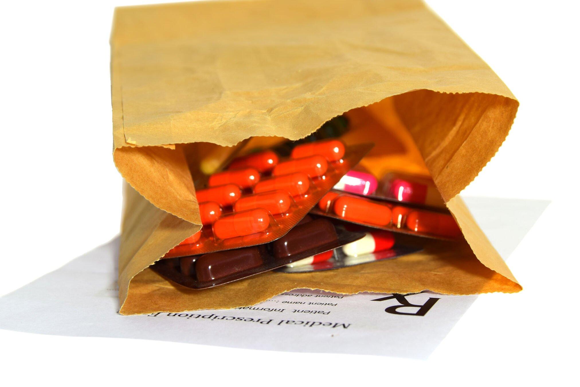 brown paper bag full of pills in blister packs