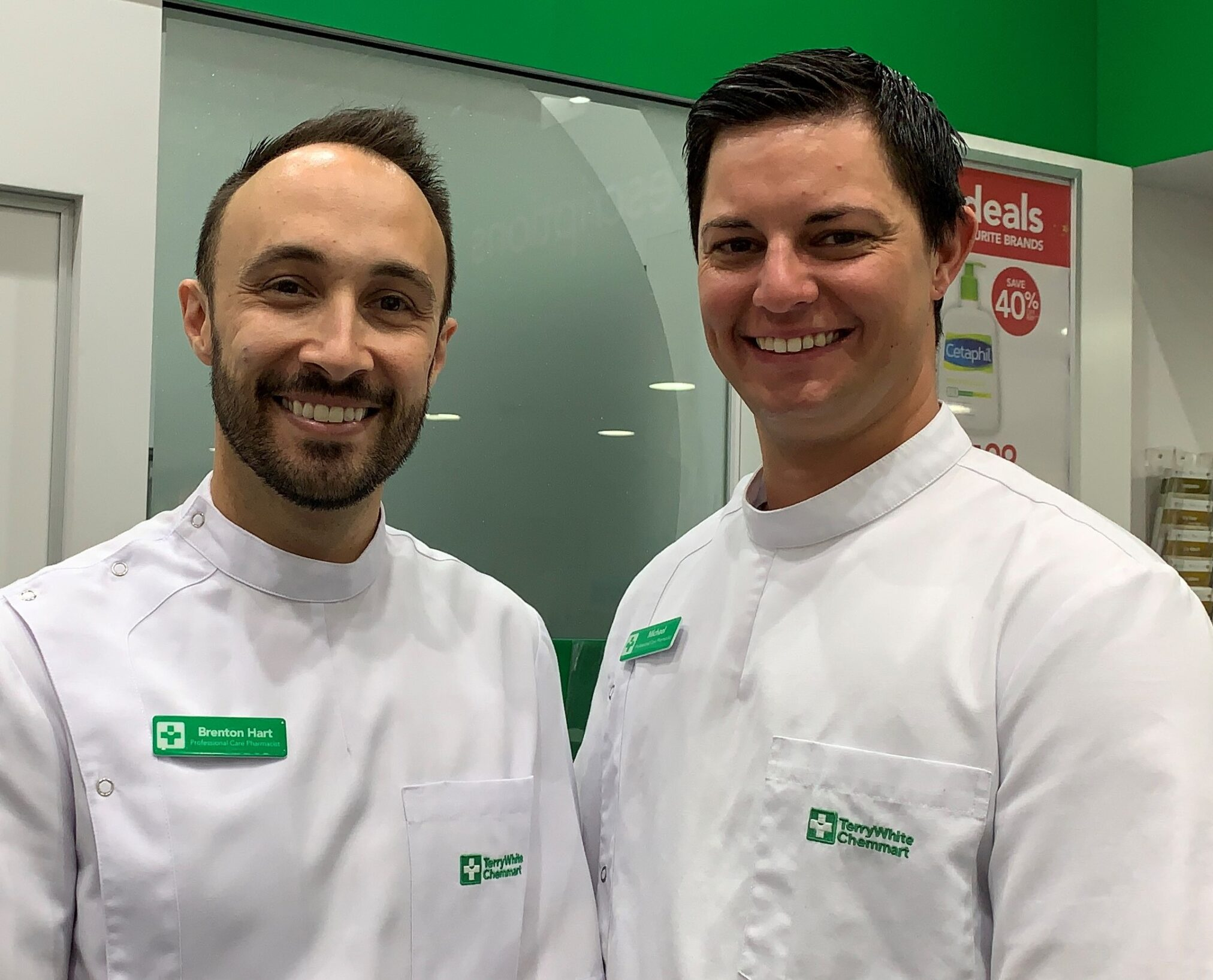 Brenton Hart and Michael Minter two men smiling in pharmacy uniforms