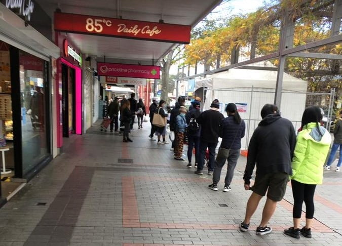 Queue of people in the street waiting outside Priceline Pharmacy